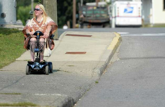Mary Sullivan tries to find safe navigation Friday morning Sept. 5, 2014 through the streets of Mechanicville, N.Y. on her motorized chair.   (Skip Dickstein/Times Union) Photo: SKIP DICKSTEIN / 00028483A