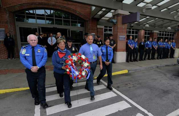 Workers representing United Airlines, American/USAir, TSA and the Albany County Sheriff's Office participate in a 9/11 wreath laying memorial Thursday morning, 8:46 AM  Sept. 11, 2014, at Albany International Airport in Colonie, N.Y. Participants from the left are: John Fletcher, TSA; Deputy Sheriff, Amy Herzog; Mary Post, American USAir;  John Ciccarelli, United Airlines and Tahara Pleasure of the TSA.  (Skip Dickstein/Times Union) Photo: SKIP DICKSTEIN / 00028557A
