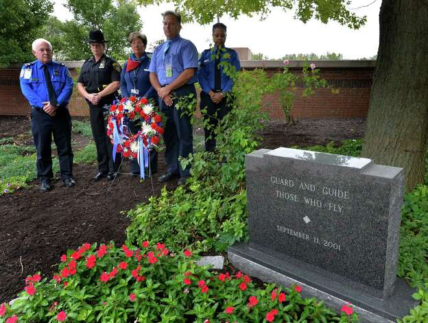 Workers representing United Airlines, American/USAir, TSA and the Albany County Sheriff's Office participate in a wreath laying at the 9/11 memorial Thursday morning, at 8:46 AM  Sept. 11, 2014, at  Albany International Airport  in Colonie, N.Y. Participants from the left are: John Fletcher, TSA; Deputy Sheriff, Amy Herzog;  Mary Post, American USAir;  John Ciccarelli, United Airlines and Tahara Pleasure of the TSA.  (Skip Dickstein/Times Union) Photo: SKIP DICKSTEIN / 00028557A