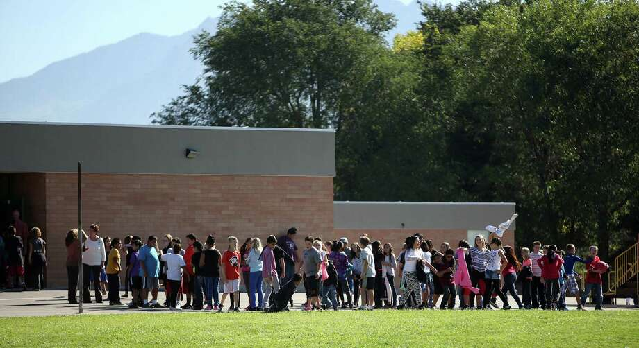 Students line up to go back inside at Westbrook Elementary School in Taylorsville, Utah, after a teacher accidentally hurt herself, officials say. Photo: Associated Press / Deseret News
