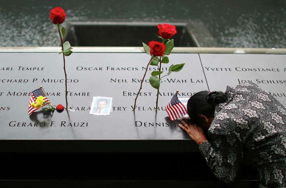 A woman grieves at her husband's memorial at the South Tower Memorial Pool during  Thursday's observances at the World Trade Center in New York. Photo: Chang W. Lee / The New York Times / Associated Press / POOL The New York Times