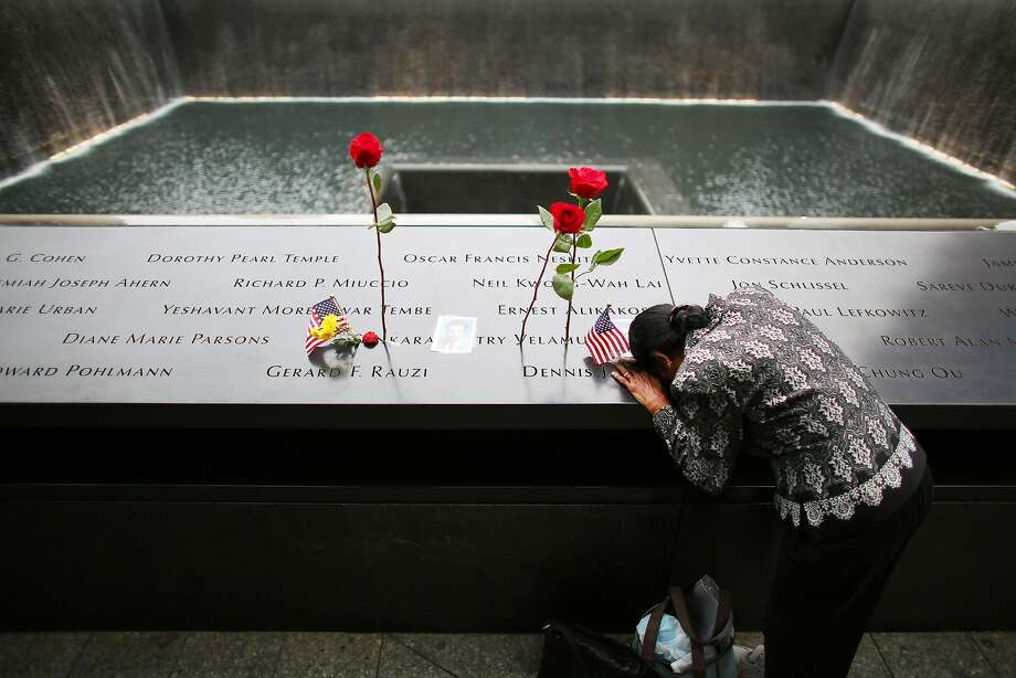 NEW YORK, NY - SEPTEMBER 11: A woman grieves at her husband's memorial at South Tower Reflecting Pool before the memorial observances held at the site of the World Trade Center before memorial observances are held at the site of the World Trade Center on September 11, 2014 in New York City. This year marks the 13th anniversary of the September 11th terrorist attacks that killed nearly 3,000 people at the World Trade Center, Pentagon and on Flight 93.  (Photo by Chang W. Lee-Pool/Getty Images) Photo: Pool, Getty Images