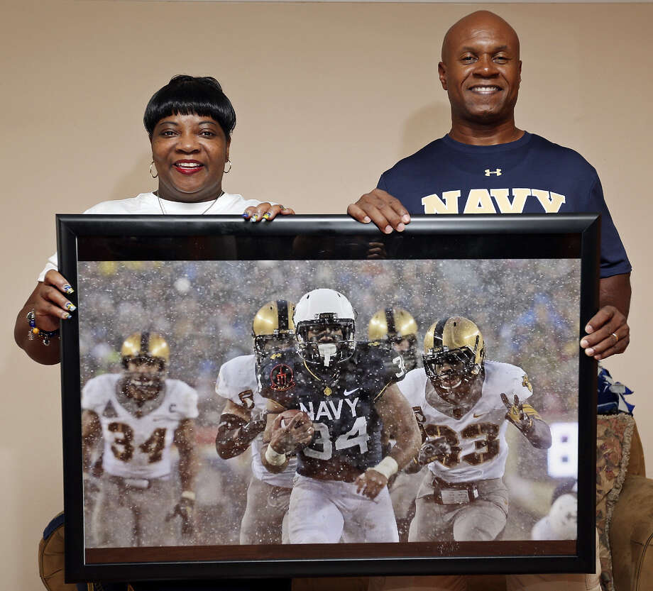 Catherine (left) and Fred Copeland hold a portrait showing their son, Navy senior fullback and Brandeis grad Noah Copeland, in action. Copeland was voted a team captain this season. Photo: Edward A. Ornelas / San Antonio Express-News / © 2014 San Antonio Express-News