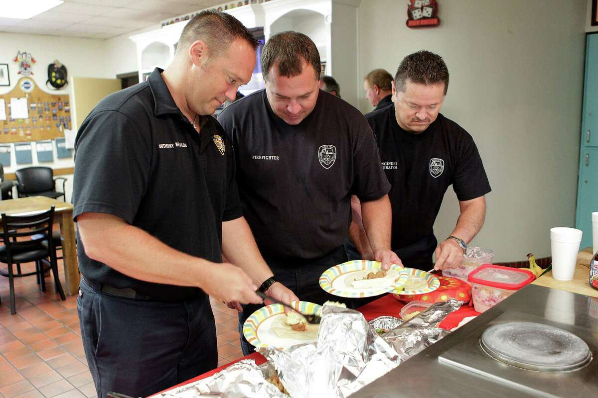 HFD engine operator Anthony Reynolds, firefighter Keith Tisdel, and engine operator Joe Hernandez help themselves to a second serving while H-E-B celebrates the 10th year of Helping Heroes where they provide breakfast for brave firefighters on Wednesday, Sept. 10, 2014, in Houston.