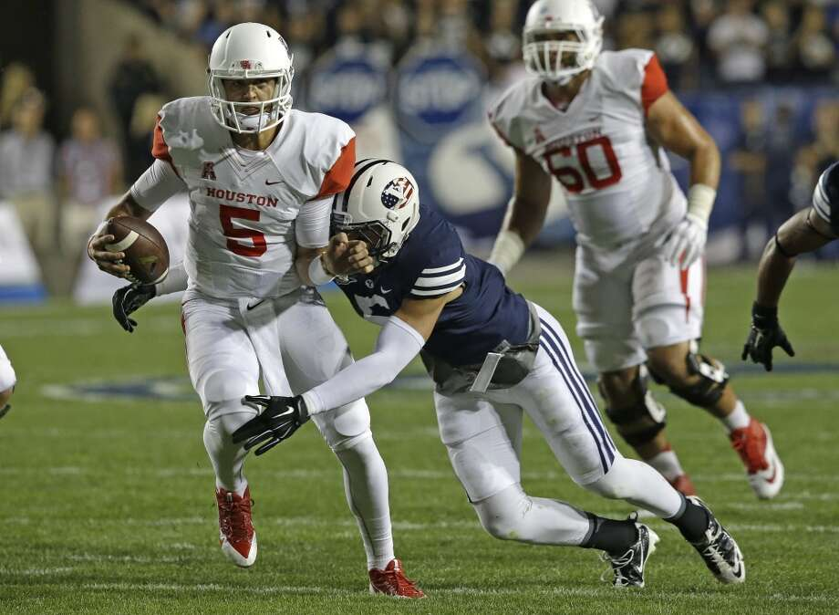 BYU linebacker Alani Fua (5) tackles Houston quarterback John O'Korn (5) in the second quarter of an NCAA college football game Thursday, Sept. 11, 2014, in Provo, Utah.(AP Photo/Rick Bowmer) Photo: Rick Bowmer, Associated Press