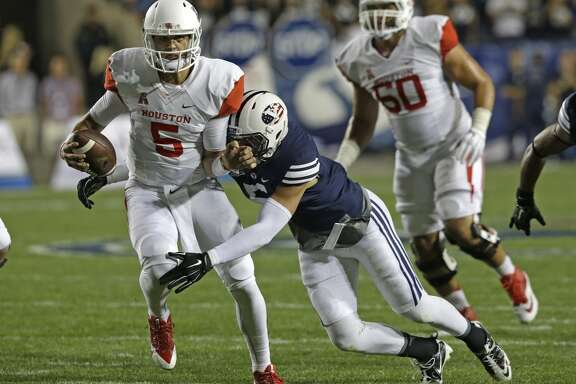 BYU linebacker Alani Fua (5) tackles Houston quarterback John O'Korn (5) in the second quarter of an NCAA college football game Thursday, Sept. 11, 2014, in Provo, Utah.(AP Photo/Rick Bowmer)