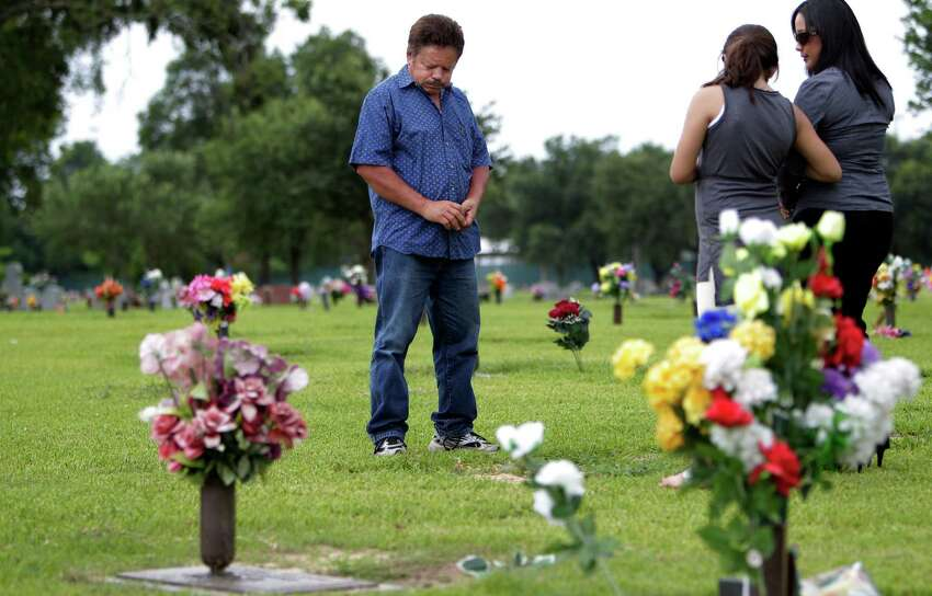 Guillermo Gomez of Houston sighs while visiting the grave site of his wife Vilma Marenco on July 15, 2014. Marenco was driving home after working the lunch shift at Pappasito's when an oilfield hauling truck loaded with heavy pipe ran a red light and crushed the passenger side of her Chevy Cavalier. Marenco was killed at the scene of the accident, an industrial intersection near her home. Inspection reports show the trucking firm had been targeted for state enforcement but kept operating without a state license. The truck that killed Marenco had at least a dozen defects and was not road-worthy, a post-accident inspection shows.