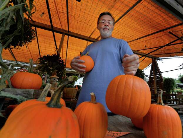 Kevin McGrath puts out some of the first pumpkins of the season at the Olde Saratoga Home and Garden stand Thursday afternoon, Sept. 11, 2014, in Saratoga, N.Y. (Skip Dickstein/Times Union) Photo: SKIP DICKSTEIN