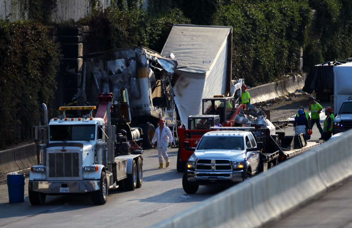 Road crews attempt to clear the wreckage after an 18-wheeler erupted in flames on the Southwest Freeway near Spur 527 on Sept. 12, 2014.