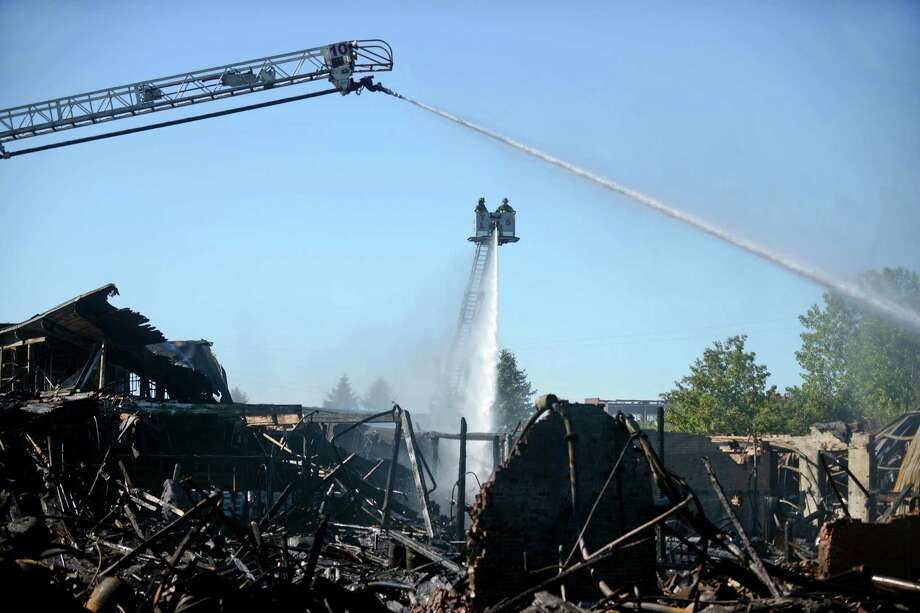 Firefighters remain on the scene of the five-alarm fire that broke out at a warehouse at 2102 Seaview Ave. on Thursday, Sept 11, 2014 in Bridgeport, Conn. The buildings, that housed a roofing company and perfume-recycling company, sustained multiple collapse areas so fire investigators had not yet entered the fire area on the early afternoon, Friday, Sept. 12th. Photo: Autumn Driscoll / Connecticut Post