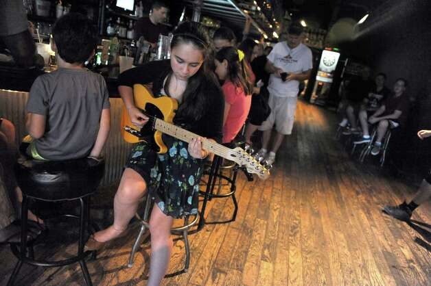 Thirteen-year-old Nora Gauna of Loudonville, left, warms up on guitar prior to The School of Rock Performance Program at The Hollow on Saturday Sept. 6, 2014 in Albany, N.Y. The School of Rock Performance Program, a group of Capital District students, will perform a set featuring music from the past 28 years of Farm Aid! Just as Farm Aid brings a wide array of musicians together to benefit our nations hard working family owned farms, School of Rock is uniting our students to perform and raise awareness and funds for Schoharie Valley Farm to School Project! At School of Rock we strive to create a wide array of musical experiences for our students. Organizing this event enabled us to bring a spotlight to playing music for a worthy cause, a value that we at School of Rock want to promote. Teaching not only music, but how to become a community minded school is a goal for our program.  (Michael P. Farrell/Times Union) Photo: Michael P. Farrell / 00028347A