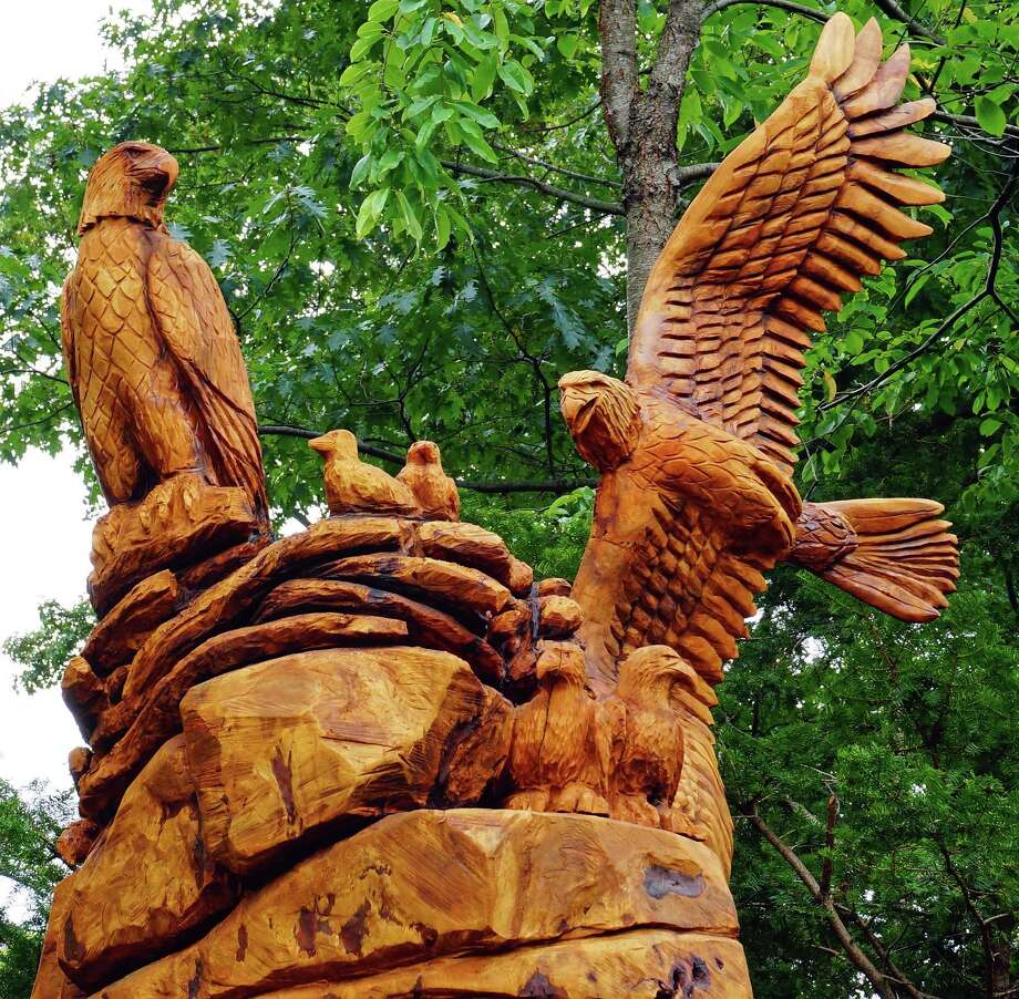 A family of eagles has landed in the town's Riverhurst neighborhood, thanks to resident Bruce Woelfle, who hired a scupltor to create the artwork using a chainsaw. The outspread wings of the male eagle measure six feet. Photo: Genevieve Reilly / Fairfield Citizen