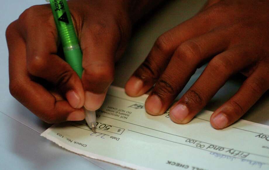 FILE PHOTO: A child write a mock check Thursday afternoon July 22, 2004 while learning about checkbook finances at the Woodard Community Center. The use of credit and debit cards has had an impact on the usage of checks. Photo: WILLIAM LUTHER, SAN ANTONIO EXPRESS-NEWS / SAN ANTONIO EXPRESS-NEWS