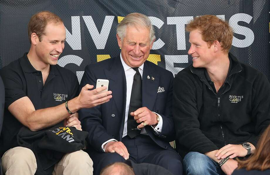 Siri, when will Dad be king?Prince Charles and his two boys are distracted from the athletic competition at the Invictus Games in London by something on William's cellphone. Photo: Chris Jackson, Getty Images