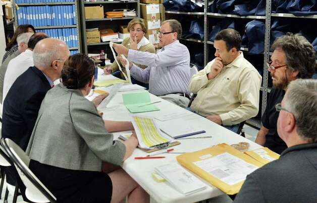 The Rensselaer County Board of Elections counts absentee ballots in the Democratic primary for city court judge Friday Sept. 12, 2014, in Troy, NY.  (John Carl D'Annibale / Times Union) Photo: John Carl D'Annibale / 00028586A