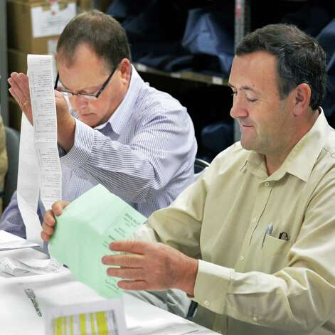 Commissions Ed McDonough, left, and Ed Bugbee check ballots as the Rensselaer County Board of Elections counts absentee ballots in the Democratic primary for city court judge Friday Sept. 12, 2014, in Troy, NY.  (John Carl D'Annibale / Times Union) Photo: John Carl D'Annibale / 00028586A