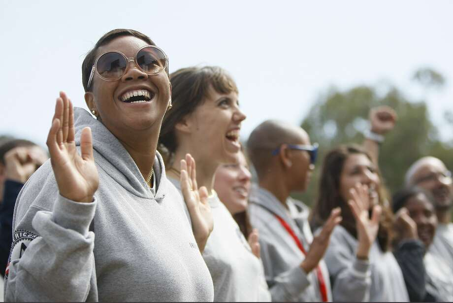 AmeriCorps members raise their hands during a swearing-in ceremony of 1,000 new volunteers led by Gov. Jerry Brown at the Presidio Institute in San Francisco. Created under President Bill Clinton, AmeriCorps has had 116,000 members. Photo: Jessica Christian, The Chronicle