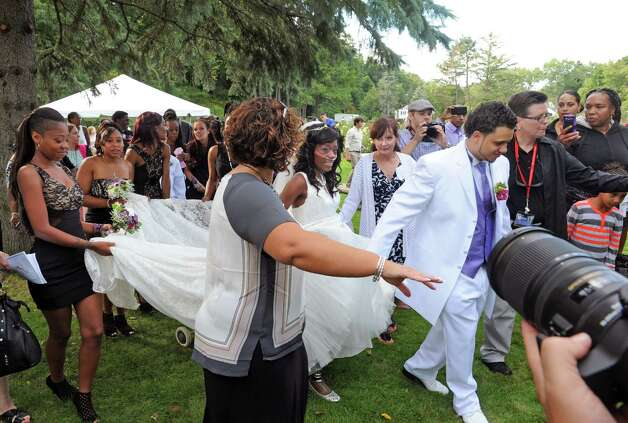 Bride Jahaysia Graham, center, and groom Jathyis Lajuett, right, walk through the crowd after being married at the Central Park Rose Garden  Friday afternoon, Sept. 12, 2014, in Schenectady, N.Y. (Michael P. Farrell/Times Union) Photo: Michael P. Farrell / 00028581A