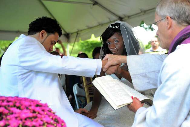 Jathyis Lajuett, left, and Jahaysia Graham are married by Rev. Henry Frueh, right, at the Central Park Rose Garden Friday afternoon, Sept. 12, 2014, in Schenectady, N.Y. Nineteen-year-old Jahaysia is a patient of The Community Hospice. (Michael P. Farrell/Times Union) Photo: Michael P. Farrell / 00028581A