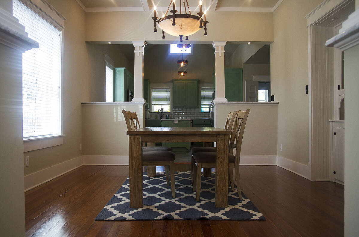 It took Cody Doege and Chad Walling three years to renovate this Tobin Hill home. They kept the original pine floors, seen here in the dining room. A trio of pendant light fixtures in the kitchen (background) are made from metal chicken feeders.
