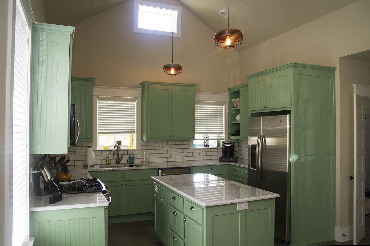 The formerly tiny kitchen now has a cathedral ceiling, lots of cabinet and counter space and a center island.