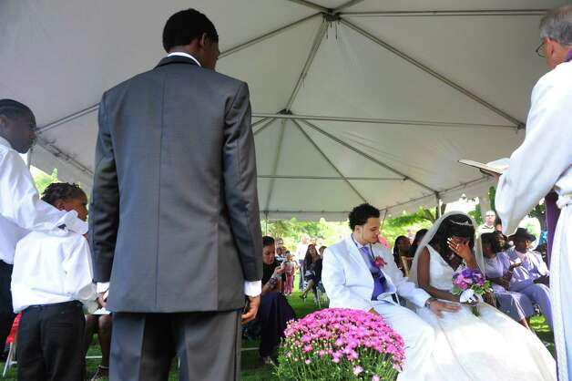 Groom, Jathyis Lajuett and bride, Jahaysia Graham, are married by Rev. Henry Frueh, right, at the Central Park Rose Garden Friday, Sept. 12, 2014, in Schenectady, N.Y. Nineteen-year-old Jahaysia is a patient of The Community Hospice. (Michael P. Farrell/Times Union) Photo: Michael P. Farrell / 00028581A