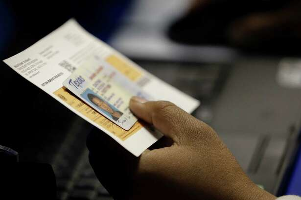 An election official checks a voter's photo ID  at an early voting polling site in Austin in February.