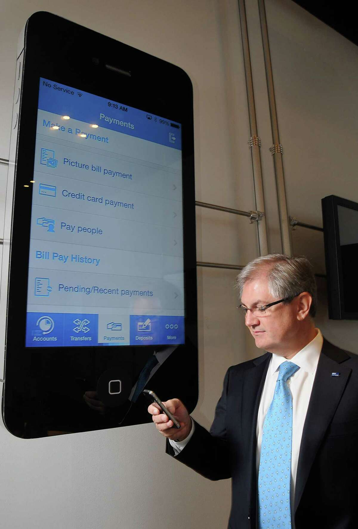 Alejandro Carriles demonstrates his bank's mobile application's features at the BBVA Compass Bank Building on Post Oak Friday Aug. 29, 2014.(Dave Rossman photo)