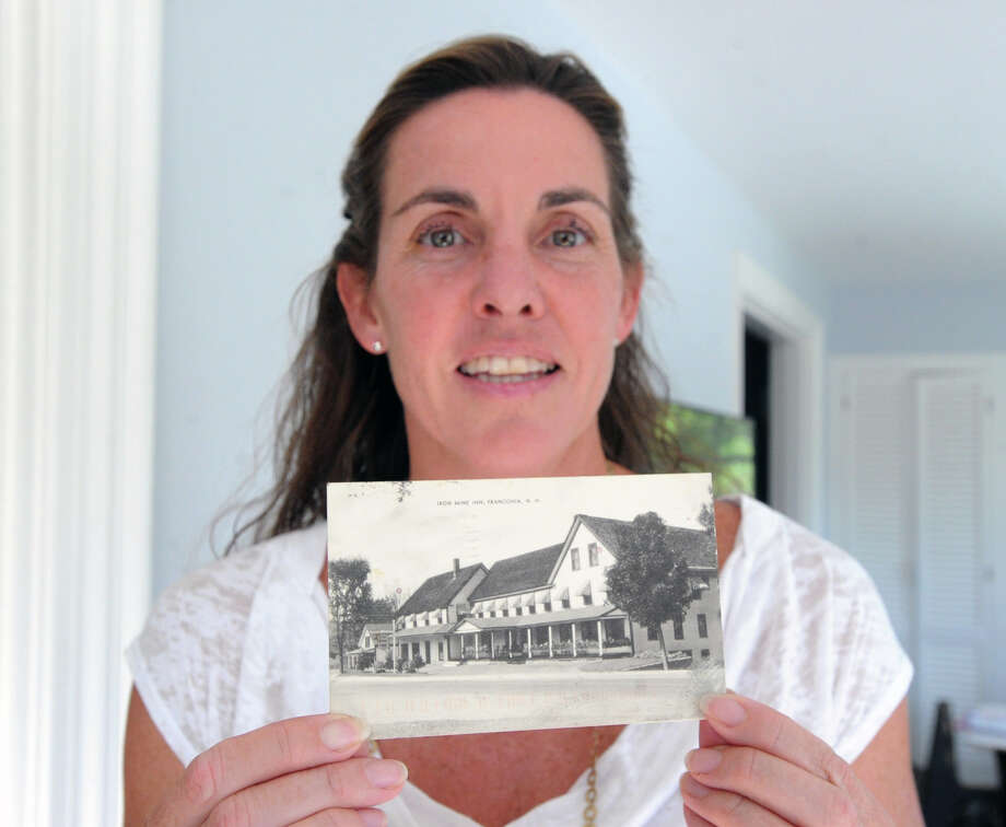 "Alicia Collier holds a postcard with a 1948 postmark that was delivered to her home at 370 Sound Beach Ave., Old Greenwich, Conn., Friday, Sept. 12, 2014. The postcard, featuring the Iron Mine Inn in Franconia, N.H., was addressed to Linda Benner at what is now the Collier's address and was signed ""Love Mommy"". Photo: Bob Luckey / Greenwich Time"