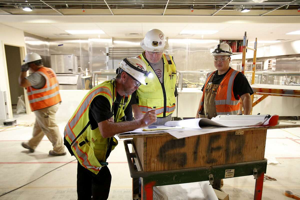 From left, Finbarr Daly, Art Perrin and Alan Chow, all of Sierra Electric, have a meeting during construction at the new St. Anthony's dining room in San Francisco, Calif., on Friday, September 12, 2014.