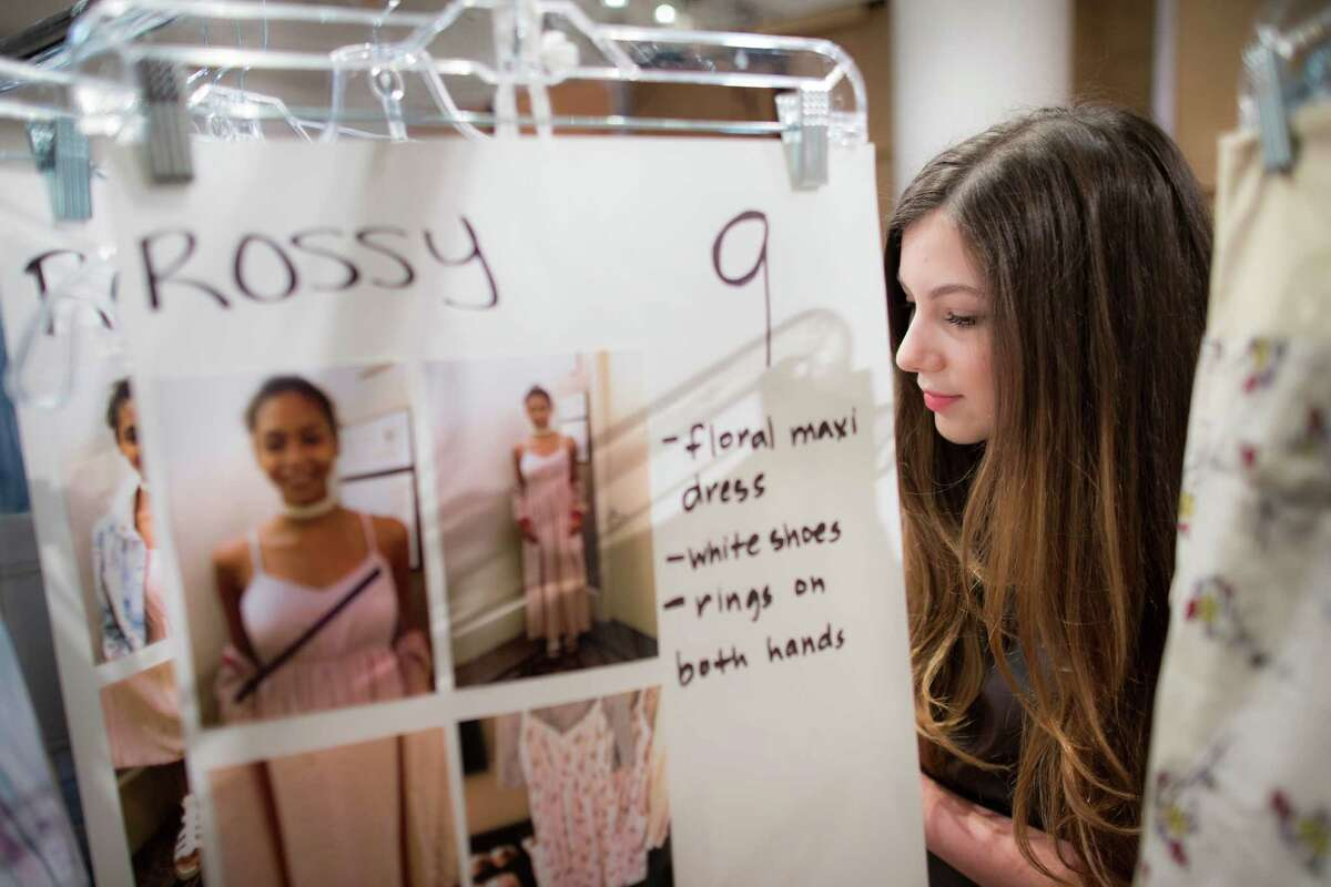 Designer Isabella Rose Taylor searches through clothing racks upon a reporters request backstage before the Spring 2015 collection is modeled during Fashion Week, Tuesday, Sept. 9, 2014, in New York.