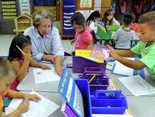 Cathy Billings, 78, of Newtown, Conn., works with Kindergartners at Morris Street School in Danbury, Conn., Friday, Sept. 12, 2014. Billings is a volunteer mentor.