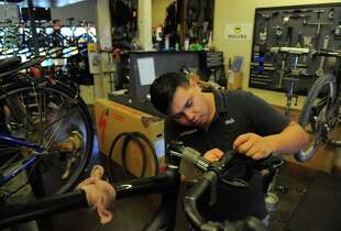 Mechanic Caesar Gomez gives a bike a full tune up at Mikes Bikes on August 21, 2014 in Sausalito, CA. Gomez is one of the many kids that has gone through Trips for Kids, a nonprofit program created by Marilyn Price two decades ago as a way to get teens from the urban Bay Area out of their neighborhoods to experience nature on mountain bikes in Marin. Gomez was subsequently placed in a shop as a working mechanic
