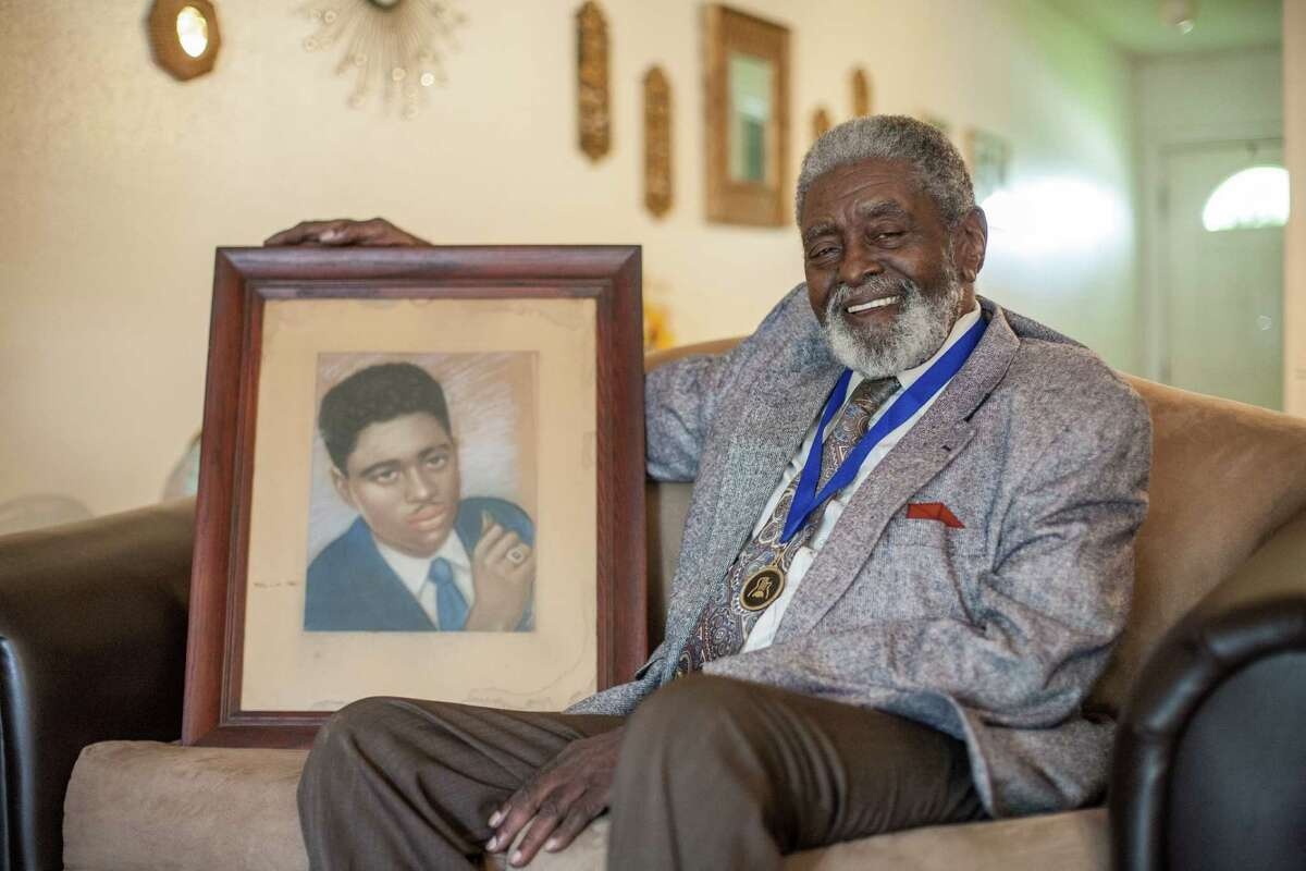 Jimmy Dotson, a Houston blues musician, poses for a portrait with a self portrait in his home Friday September 12, 2014 in Houston, TX. Dotson drew the picture of himself when he was 19 years old and it hangs over his fireplace today. (Michael Starghill, Jr.)