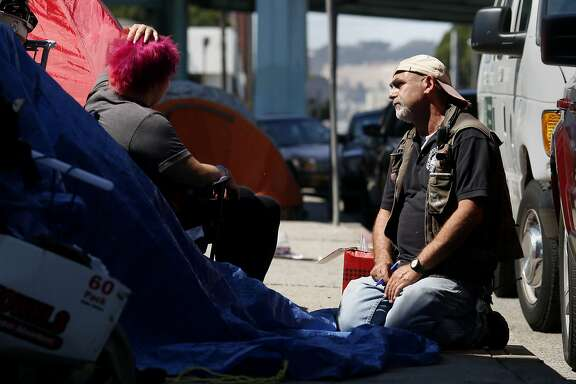 Psychiatric social worker Jason Albertson talks with a homeless woman about getting help Thursday September 11, 2014 in San Francisco, Calif. The Homeless Outreach Team is being cut back by the health department as it shifts from offering housing, of which there is little available right now, to offering medical care on the streets. Veteran psychiatric social worker Jason Albertson is beginning to get the word out to his homeless clients.