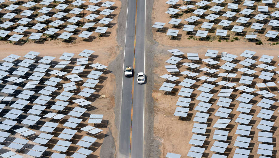 Vehicles travel on a road between rows of heliostats at the Ivanpah Solar Electric Generating System on March 3, 2014 in the Mojave Desert in California near Primm, Nevada. The largest solar thermal power-tower system in the world, owned by NRG Energy, Google and BrightSource Energy, opened recently in the Ivanpah Dry Lake and uses 347,000 computer-controlled mirrors to focus sunlight onto boilers on top of three 459-foot towers, where water is heated to produce steam to power turbines providing power to more than 140,000 California homes. Photo: Ethan Miller, Staff / Getty Images / ONLINE_CHECK