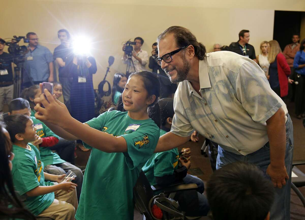 Francisco Middle School 6th grader Renee Huang, takes a selfie with Salesforce CEO Marc Benioff before the presentation at the Rincon Center in San Francisco, Calif., on Friday Sept. 12, 2014. Salesforce CEO Marc Benioff announces a new $5 million donation from Benioff which included money for 1,500 iPads for the city's twelve public middle schools as well as $100,000 for each middle school principal.