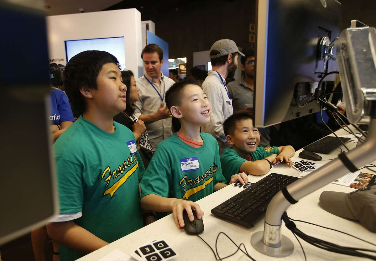 Francisco Middle School students Evan Lum, Timothy Dare, and Benjamin Nhan check out one of the booths during the volunteer fair put on by Salesforce at the Rincon Center in San Francisco, Calif., on Friday Sept. 12, 2014. Salesforce CEO Marc Benioff announces a new $5 million donation from Benioff which included money for 1,500 iPads for the city's twelve public middle schools as well as $100,000 for each middle school principal.