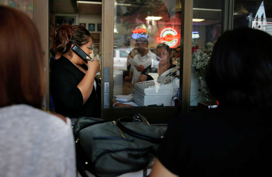 Julieta Martinez, La Taqueria manger, takes orders on the phone while working at the cash register at  La Taqueria on Wednesday, September 10,  2014 in San Francisco, Calif. Photo: Lea Suzuki, Staff / The Chronicle / ONLINE_YES