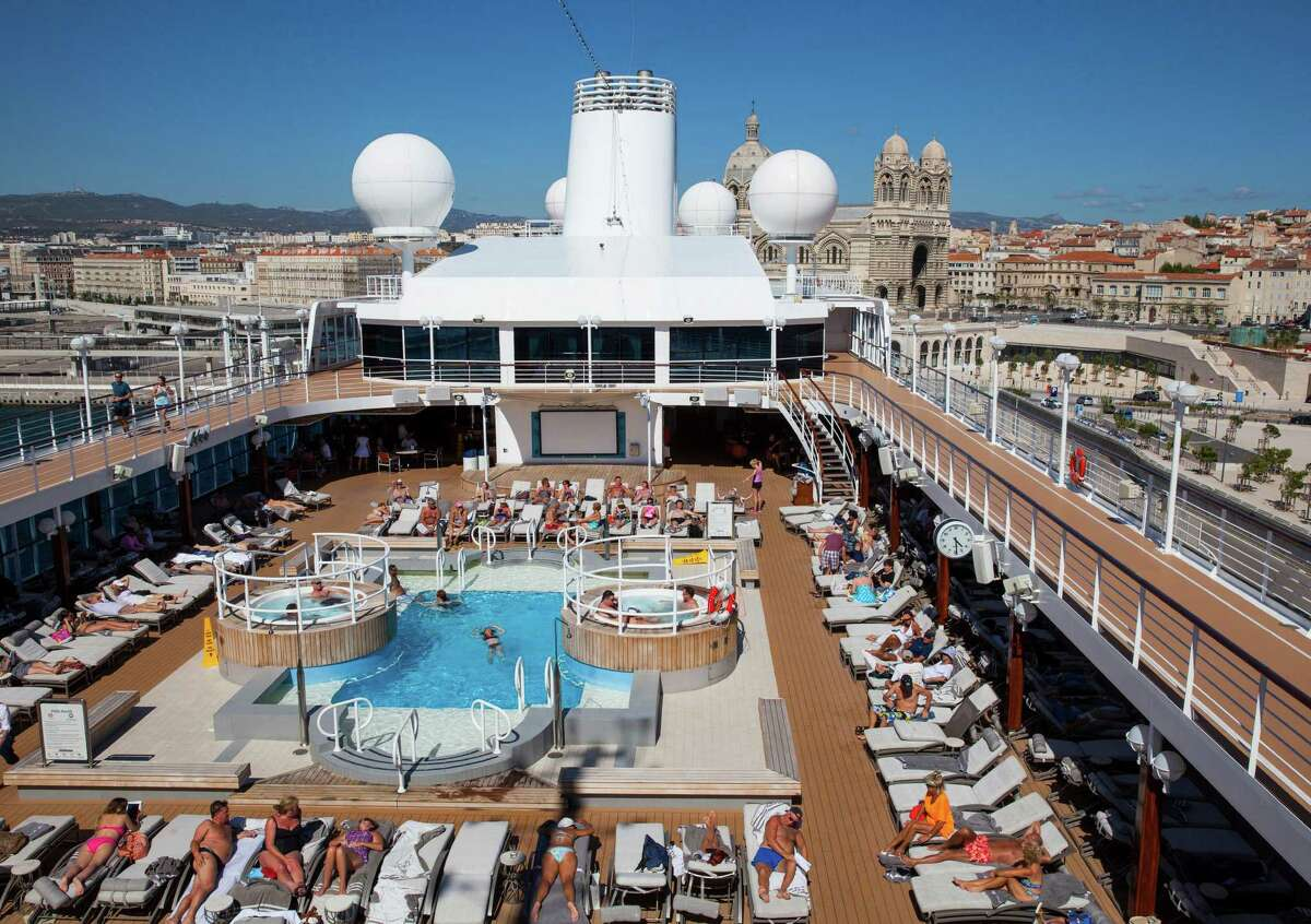 Guests on board the Azamara Quest lay out by the pool as the ship is docked in Marseille, France, during a Mediterranean cruise.