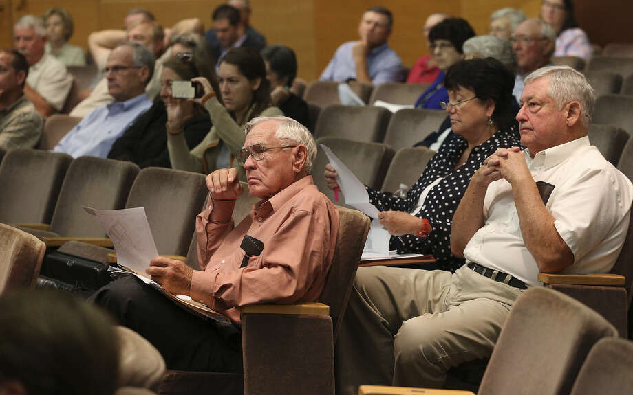 Citizens examine documents passed into the audience about a planned oil-field waste facility in Nordheim during a hearing Wednesday by examiners for the Texas Railroad Commission. Photo: Tom Reel / San Antonio Express-News