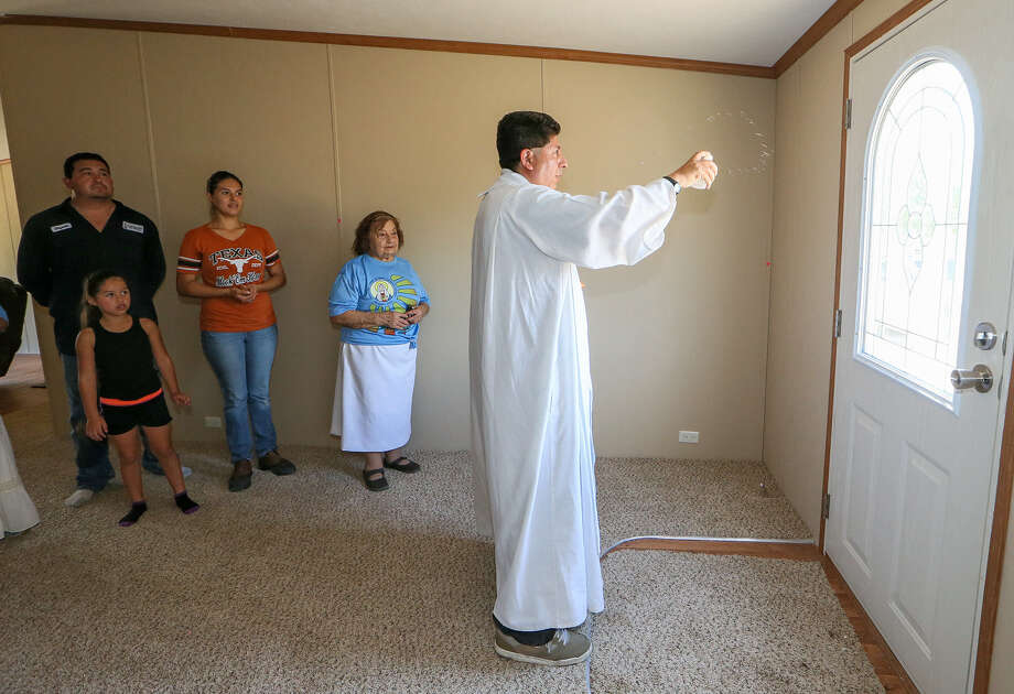 Father Jesús Camacho, pastor of Immaculate Heart of Mary Catholic Church in Pearsall, sprinkles holy water as he blesses the home of James and Crystal Elizondo (left), standing with their daughter Leileneo Cuevas, 5, and Alma Salinas. Members of the congregation also went door to door to invite people to attend Mass. Photo: Photos By Marvin Pfeiffer/ Express-News / Express-News 2014