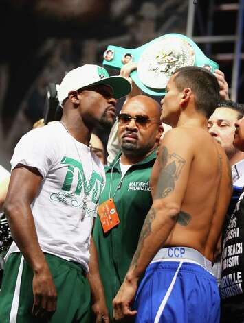 LAS VEGAS, NV - SEPTEMBER 12:  WBC/WBA welterweight champion Floyd Mayweather Jr. (L) and Marcos Maidana face off during their official weigh-in at the MGM Grand Garden Arena on September 12, 2014 in Las Vegas, Nevada. Mayweather Jr. will defend his titles against Maidana on September 13 in Las Vegas.  (Photo by Al Bello/Getty Images) ORG XMIT: 502694237 Photo: Al Bello / 2014 Getty Images