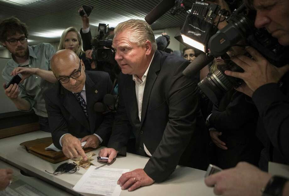 Doug Ford (center) submits his papers to enter the Toronto mayoral race after the withdrawal of his brother, Rob Ford, who's seeking treatment for a tumor in his abdomen. Photo: Chris Young / Canadian Press / The Canadian Press