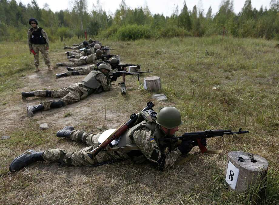 Ukrainian soldiers perform exercises at a military training center outside Zhytomyr, which is about 100 miles west of Kiev. Photo: Sergei Chuzavkov / Associated Press / AP