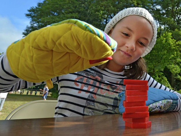 Daniella Velazquez participates in the Tangram Challenge, stacking small items using cooking gloves as a handicap, during the fifth grade science Human Body Systems kick-off at the Guilderland Elementary School Friday morning Sept. 12, 2014 in Guilderland, N.Y.  (Skip Dickstein/Times Union) Photo: SKIP DICKSTEIN / 00028573A