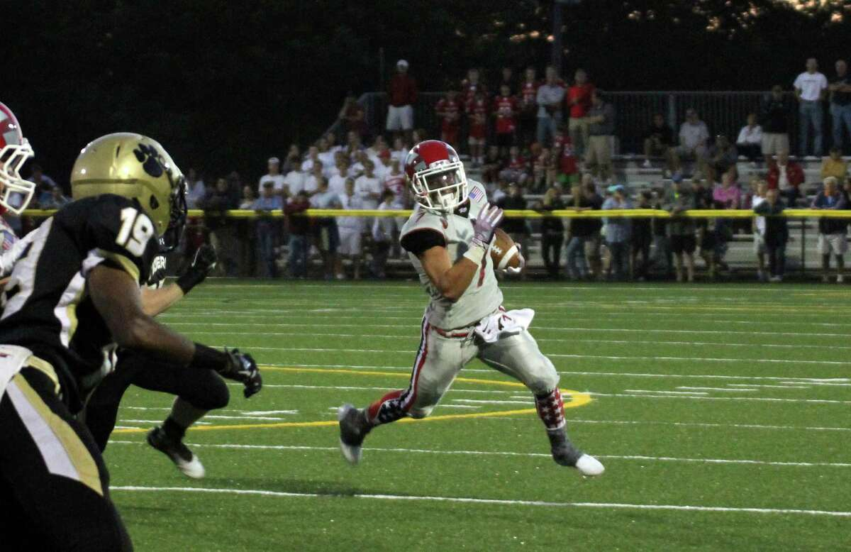 Alex LaPolice carries a pass for the New Canaan Rams against Daniel Hand High School.