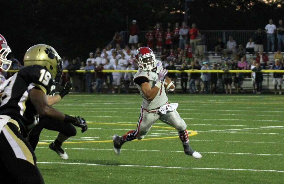 Alex LaPolice carries a pass for the New Canaan Rams against Daniel Hand High School. Photo: Megan Spicer, Ashley Varese / New Canaan News