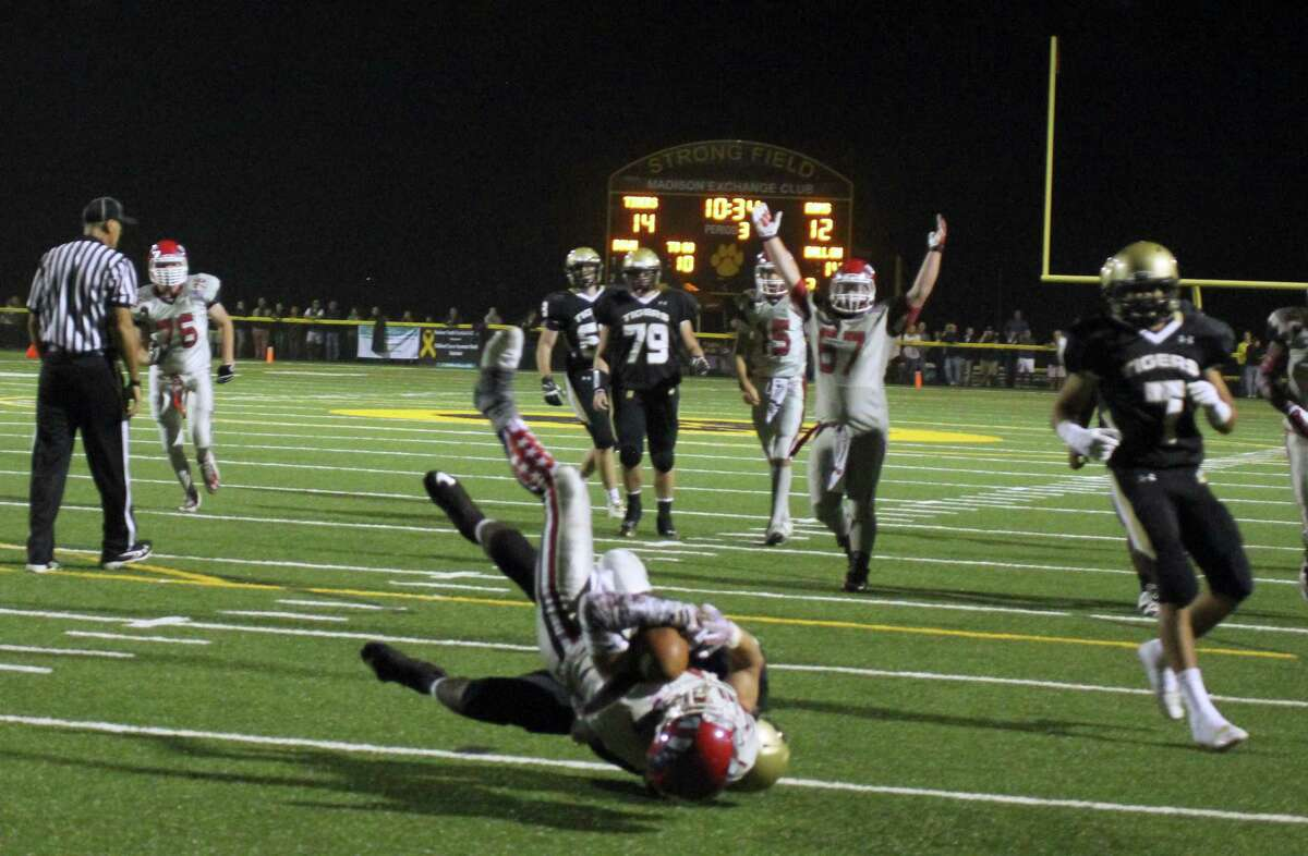 Alex LaPolice completes a touchdown for the New Canaan Rams on Sept. 12 against Daniel Hand High School.