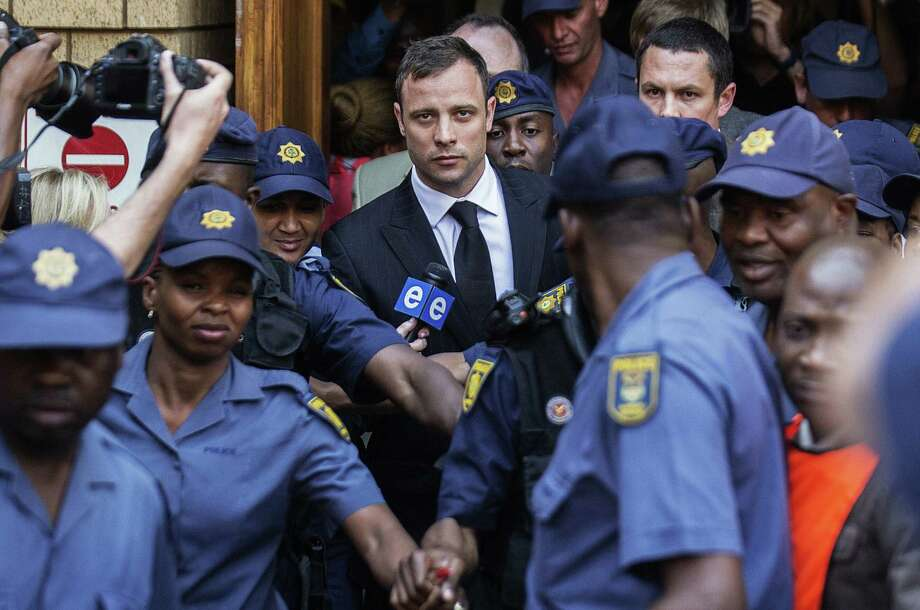 South African Paralympic athlete Oscar Pistorius (center) leaves the High Court in Pretoria after being found guilty of culpable homicide in the death of his girlfriend. Photo: Gianluigi Guercia / Getty Images / AFP